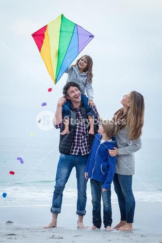 Cheerful family with kite at sea shore