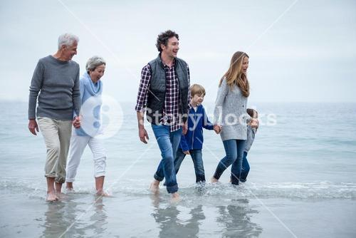 Multi-generation family walking in shallow water at beach