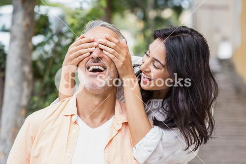 Cheerful woman covering eyes of man