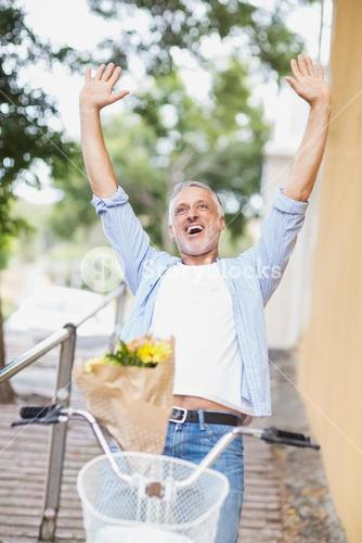 Excited man with arms raised and bicycle