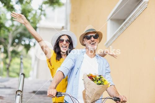Man cycling with excited woman