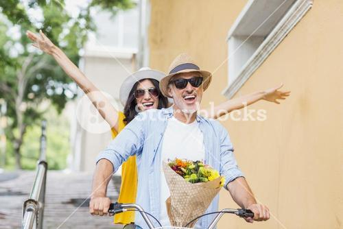 Cheerful couple cycling in city