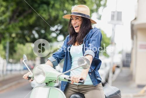 Excited woman riding moped