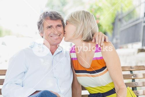 Blonde hair woman kissing man in park
