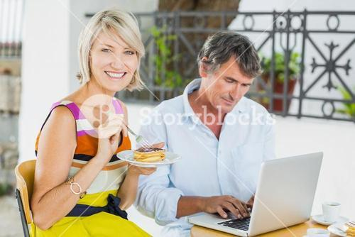 Portrait of woman eating food with man using laptop