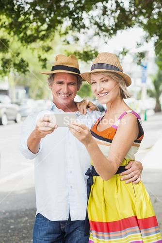 Portrait of happy couple with cellphone