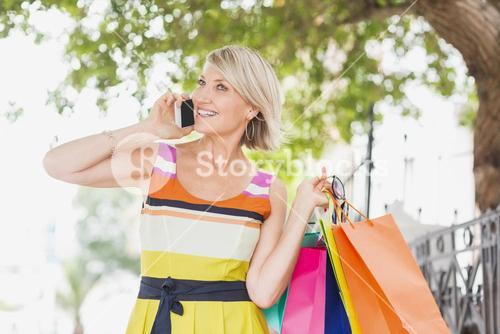 Happy woman talking on phone with shopping bags