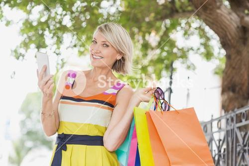 Portrait of happy woman using cellphone with shopping bags