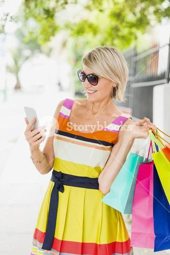 Happy woman using cellphone with shopping bags