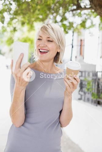 Cheerful woman looking at cellphone