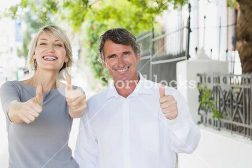 Portrait of couple with thumbs up