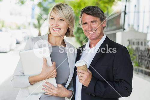 Portrait of business people with coffee and tablet