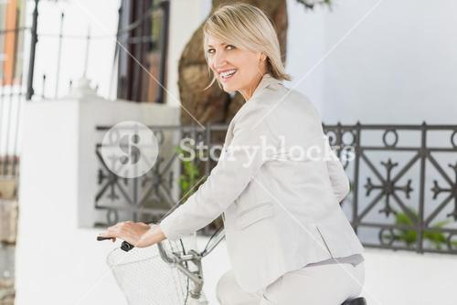 Portrait of happy businesswoman cycling