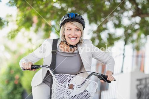 Cheerful businesswoman cycling