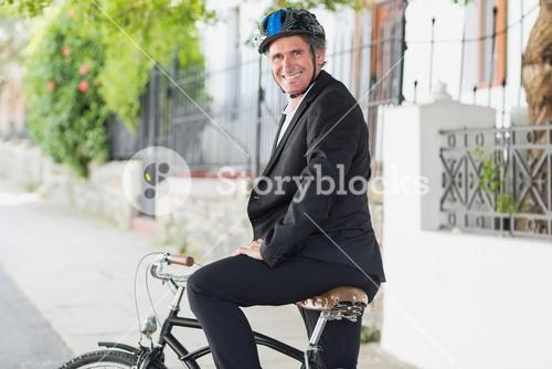 Portrait of businessman sitting on bicycle