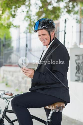 Happy businessman using cellphone on bicycle