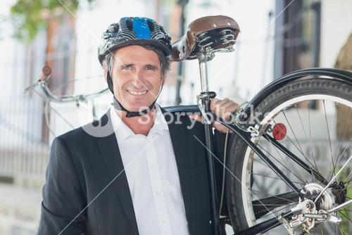 Portrait of businessman carrying bicycle