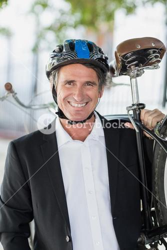 Portrait of happy businessman carrying bicycle