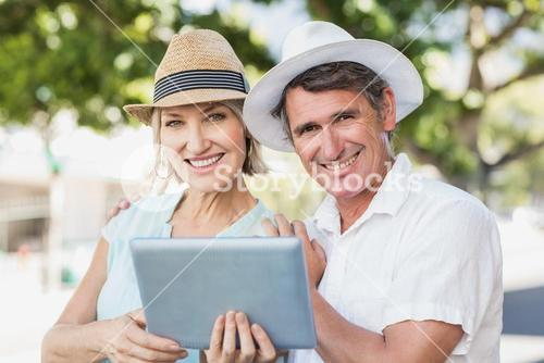 Portrait of couple using digital tablet