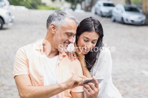 Couple using phone at street