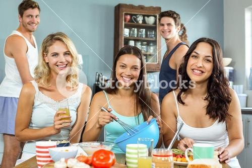 Happy male and female friends cooking together in kitchen
