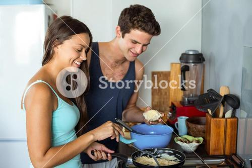 Couple cooking food in kitchen at home