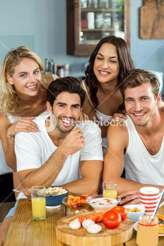 Smiling young couples at breakfast table in kitchen