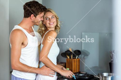 Loving man embracing woman while cooking food in kitchen
