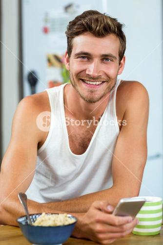Handsome young man using mobile phone at breakfast table