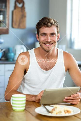 Smiling man using tablet PC at breakfast table