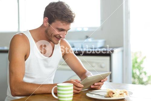 Smiling man using tablet computer at breakfast table