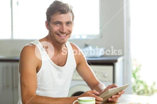 Young man using tablet PC at breakfast table