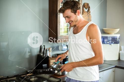 Happy man cooking food in kitchen