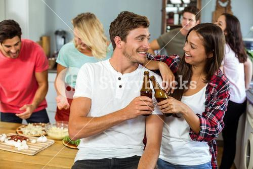 Happy young couple toasting beer bottles at home