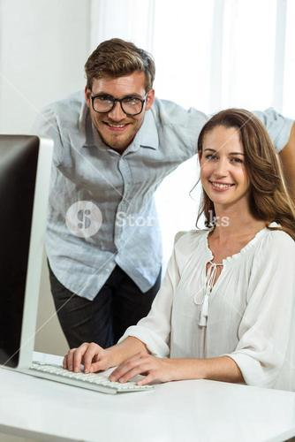 Portrait of male and female collegues using computer at office