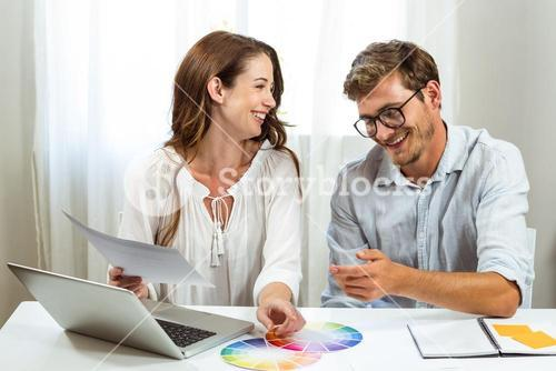 Happy male and female colleagues discussing colour samples at creative office