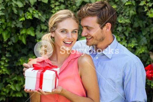 Romantic man giving gift to surprised woman
