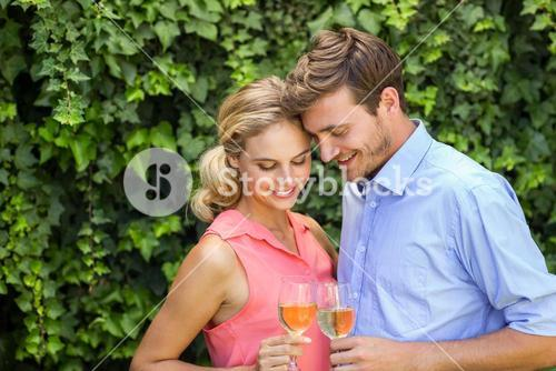 Romantic couple toasting wineglasses at front yard