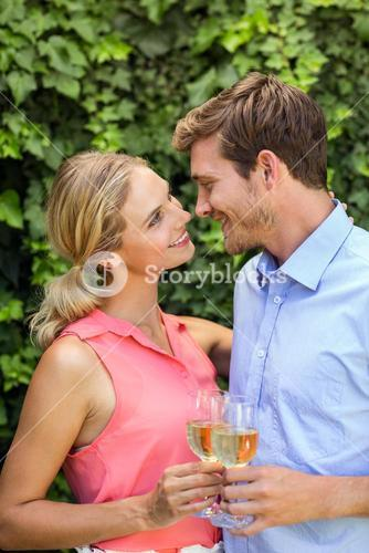 Couple toasting wineglasses at front yard