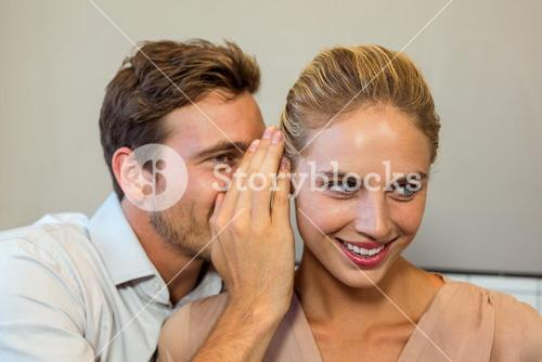 Man whispering to female colleague in office