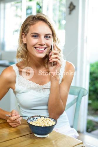 Portrait of smiling woman talking on phone at home