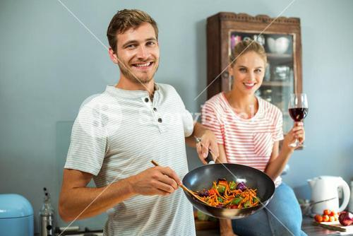 Portrait of happy couple cooking food