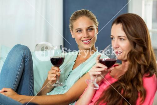 Portrait of young woman with friend enjoying wine