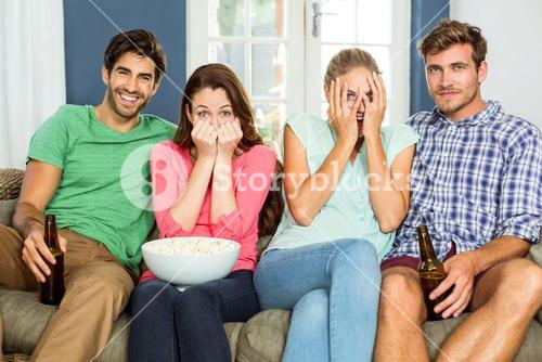 Portrait of scared women with male friends at home