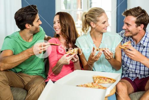Smiling friends enjoying pizza