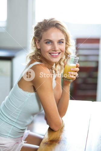 Portrait of smiling woman holding juice glass