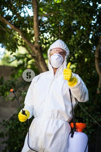 Man showing thumbs up while holding pesticide sprayer