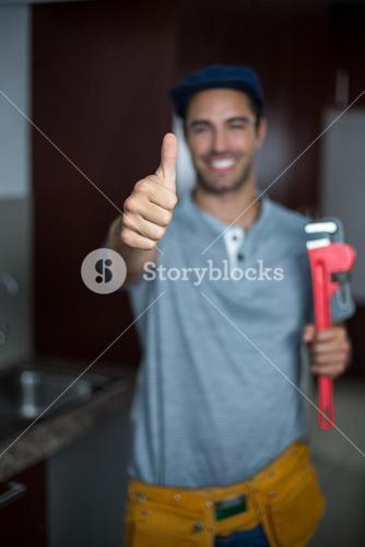 Cheerful man showing thumbs up while holding pipe wrench