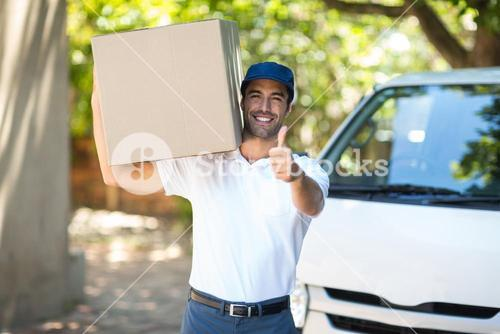 Portrait of smiling delivery man showing thumbs up