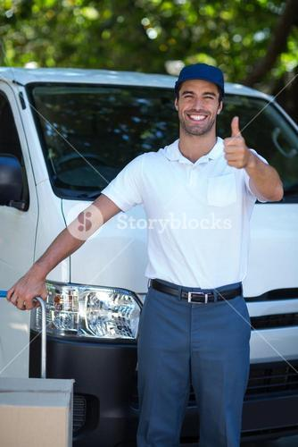 Portrait of happy delivery man showing thumbs up